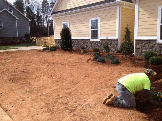 EnviraScape LLC | Landscaping progress with shrubbery and laying down sod on the side of a home