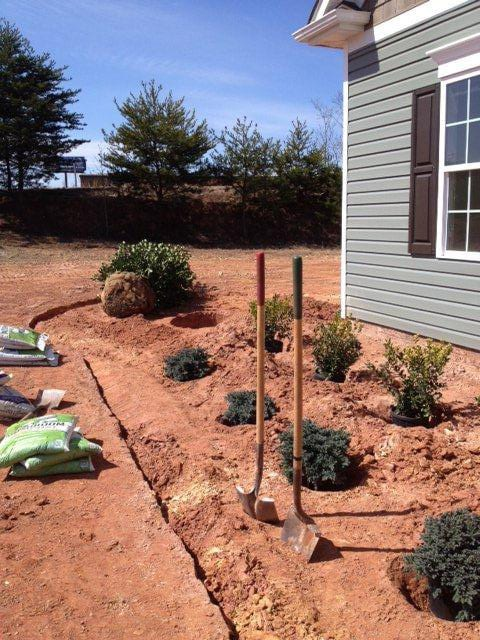 EnviraScape LLC | Landscaping progress with shrubbery on the side of a home