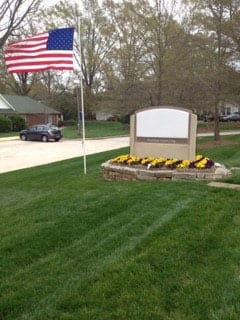 EnviraScape LLC | Floral landscaping with mulch surrounding a business sign