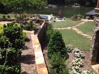 EnviraScape LLC | Stone pathways with trees and shrubs lining a nicely manicured lawn of green grass