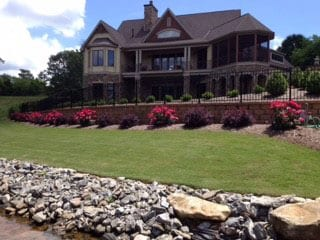 EnviraScape LLC | Bushes and bright flowers with a stone setting in front of a large Victorian style home