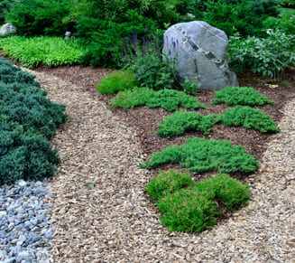 EnviraScape LLC | Landscaping with mulch and lush, green bushes with rocks