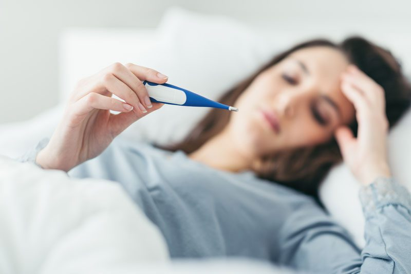 Riverview Family Medicine | Woman lying in bed ill looking at a thermometer and feeling her forehead