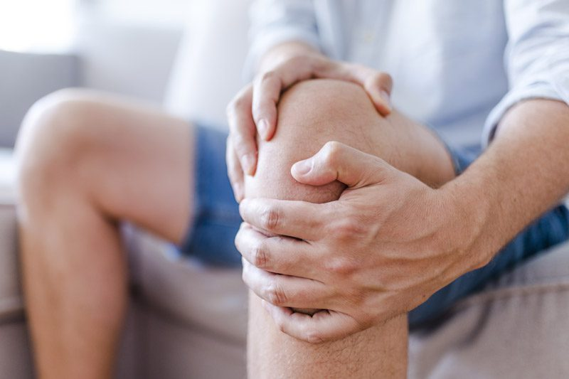 Riverview Family Medicine | Gentleman waiting to be seen by a doctor in a waiting room holding his injured knee with his hands