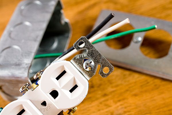 Now Electric   electrical outlet with various parts on wooden table
