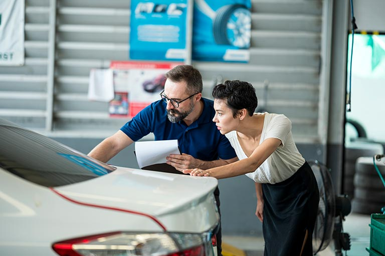 Carolina Collision tech answering questions. Carolina Collision tech explaining damage of car exterior to customer at Auto Repair Center. Business hour 24/7 service coverage. Customer Service, Quality of Service.