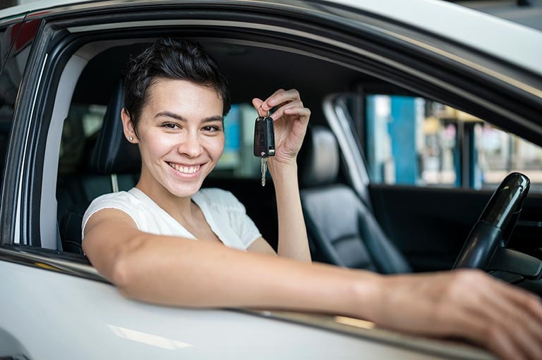 A Happy women customer holding a car key in the Carolina Collision shop testing car after repairing complete.