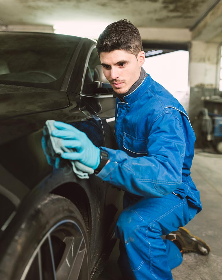 Carolina Collision mechanic cleaning a car in a workshop