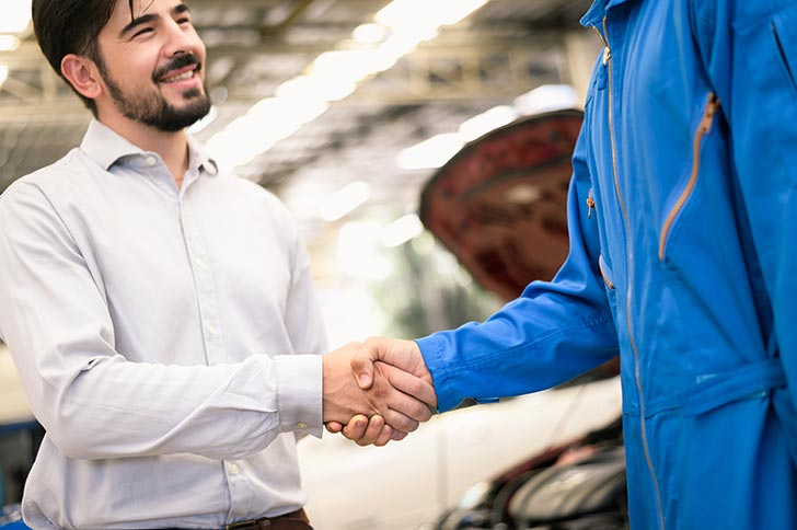 Carolina Collision technician shaking hands with vehicle owner customer after sending car for repairing or check at Carolina Collision And Frame Service.