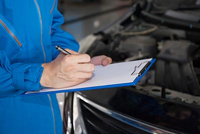 Carolina Collision mechanic taking a note and examining a vehicle