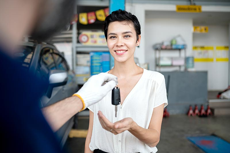 Shot of Carolina Collision Mechanic giving the car keys to his female customer in workshop at auto repair center. Quality of Service, Customer Satisfaction.
