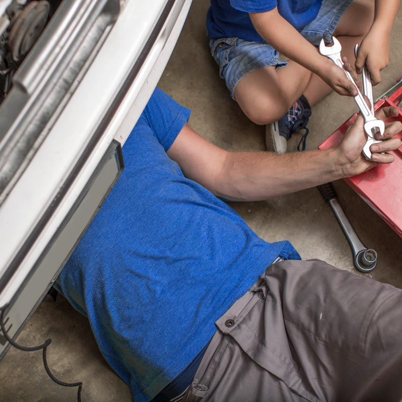 Son helping father in home garage working on car