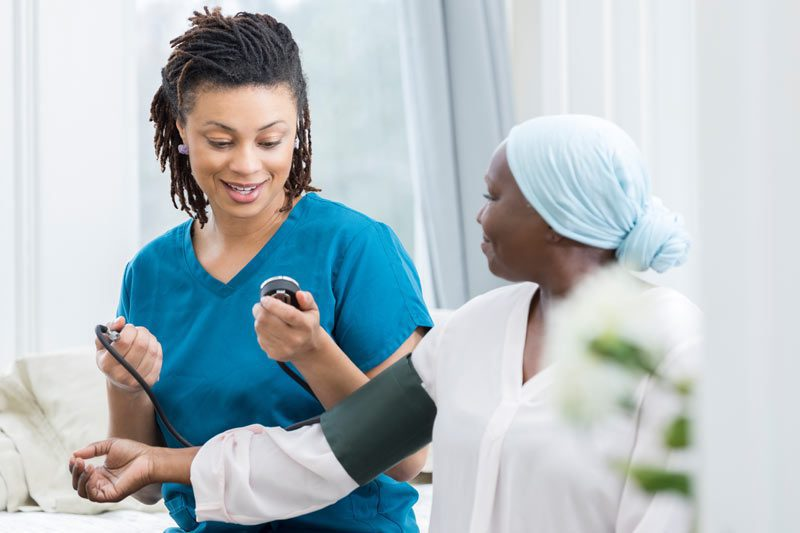 Riverview Hospice and Palliative Care LLC | Nurse taking blood pressure of a patient with a stethoscope in the patient's home