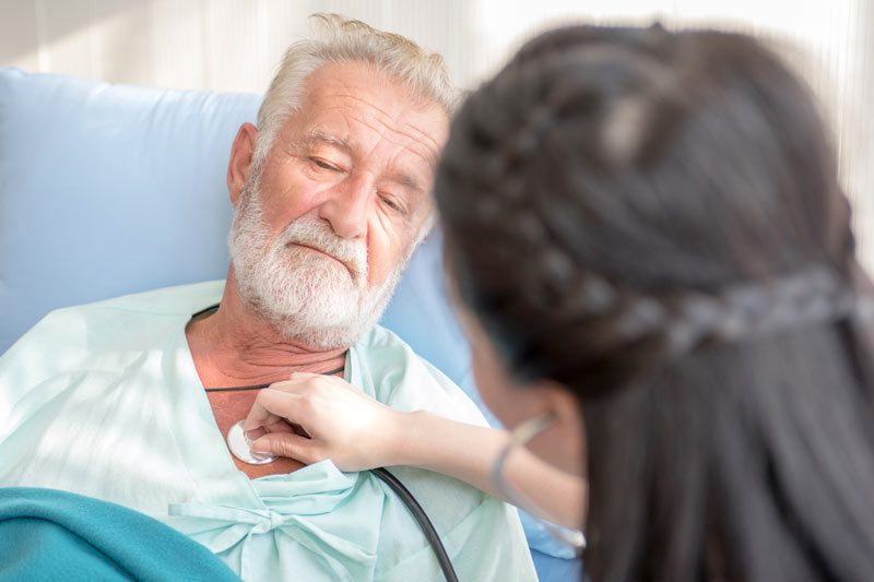 Riverview Hospice and Palliative Care LLC | Nurse listening to an older man's heartbeat with a stethoscope as he lies in bed