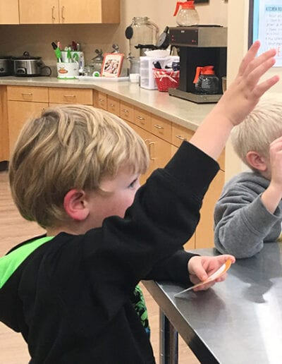 Creative Kids Fort Mill | inquisitive child raising hand in class
