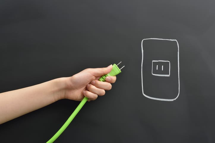 Palmetto Electrical Contractors | hand holding a bright green plug
