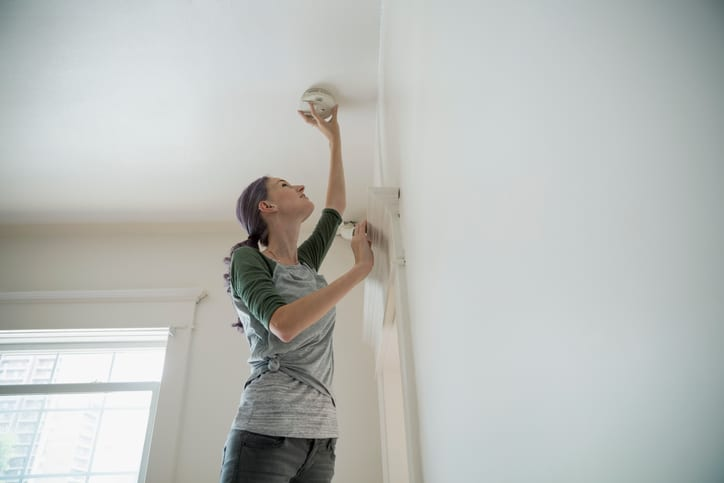 Palmetto Electrical Contractors | woman changing batteries in a smoke alarm