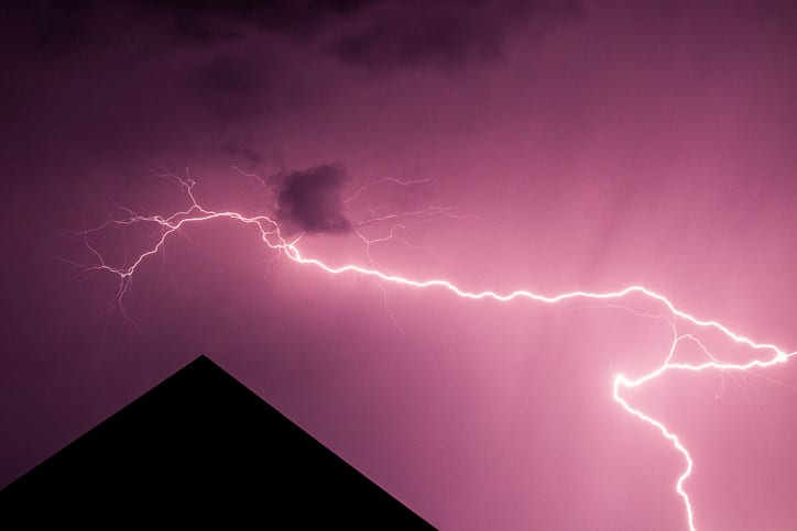 Palmetto Electrical Contractors | lightning over a roof against a dark red sky