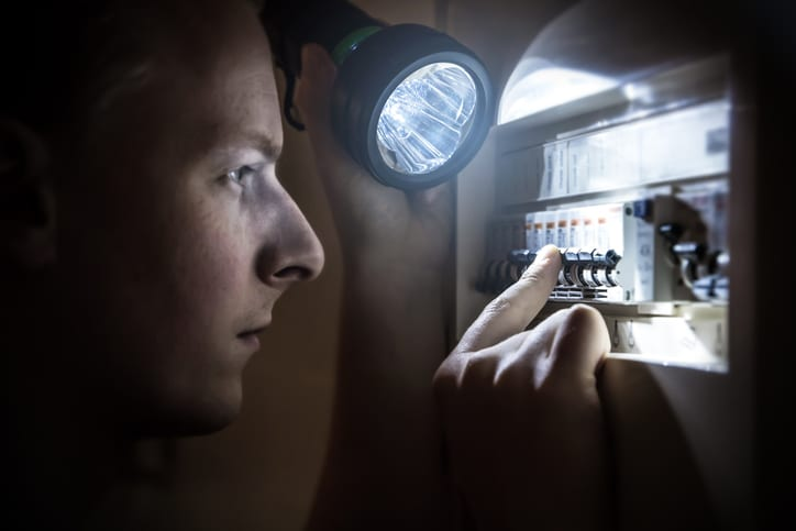 Palmetto Electrical Contractors   man with flashlight restoring power on a circuit breaker